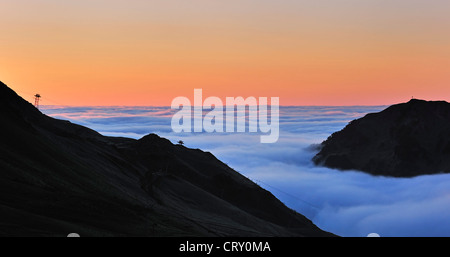 View over mountains covered in mist at sunrise seen from the mountain pass Col du Tourmalet, Hautes-Pyrénées, Pyrenees, - Stock Photo