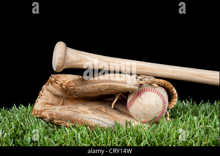 Baseball glove, ball, and bat laying on grass with a black background for placement of copy. - Stock Photo