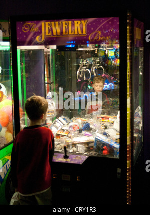 Boy age 8 playing the Jewelry Box crane machine arcade claw game. Grand Slam Amusement Center Burnsville Minnesota - Stock Photo