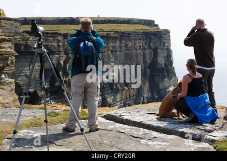 Birdwatchers using binoculars and a telescope to watch Puffins and colony of seabirds nesting on cliffs. Noup Head - Stock Photo