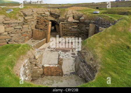 Excavations of primeval dwelling with connecting passage in prehistoric Neolithic village at Skara Brae Orkney Islands - Stock Photo