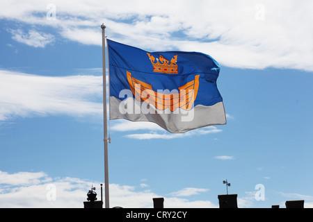 fluttering flag of Helsinki against blue sky - Stock Photo