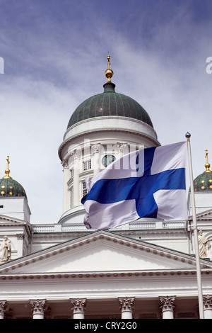 fluttering national flag of Finland against Helsinki Cathedral, most prominent building and symbol of the city - Stock Photo
