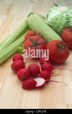 fresh raddish and vegetables over pine wood table closeup - Stock Photo