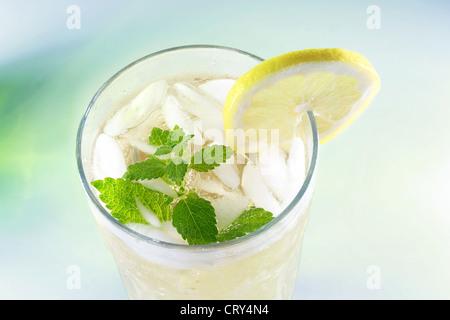 Ice-cold Lemonade with fresh slice of lemon and lemon balm (mint) - Stock Photo