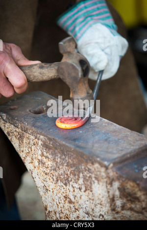 Blacksmith making decorative iron work using hammer and anvil - Stock Photo