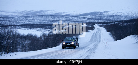 Car with trailer towing snowmobile through arctic wilderness at nightfall by Kilpisjarvi on route from Norway into - Stock Photo