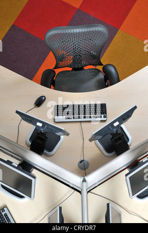 Seen from above an office hot desk with computer screens keyboards and chair - Stock Photo