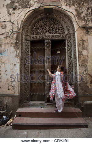Woman in colourful traditional in front of a carved wooden doorway - Stock Photo