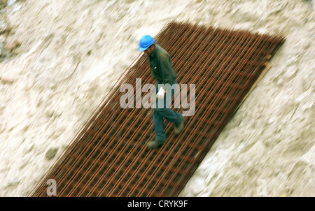 Construction worker runs down on a steel grid - Stock Photo