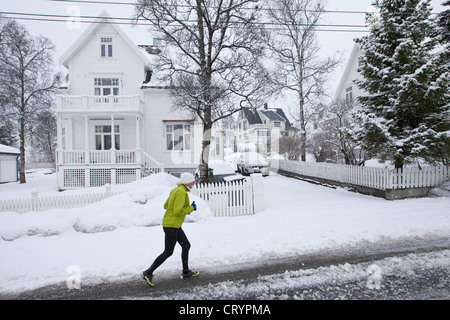 Local woman jogging in Jonas Lies Gate, the elegant residential area of Tromso within the Arctic Circle in Northern - Stock Photo