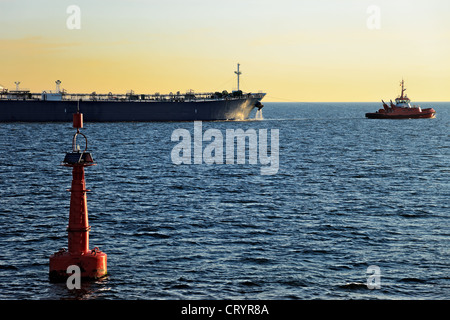 Red buoy on the fairway and outbound tanker in the sea. - Stock Photo
