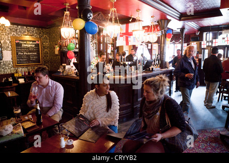 People having a drink in the Duke of York pub in Victoria, London UK - Stock Photo