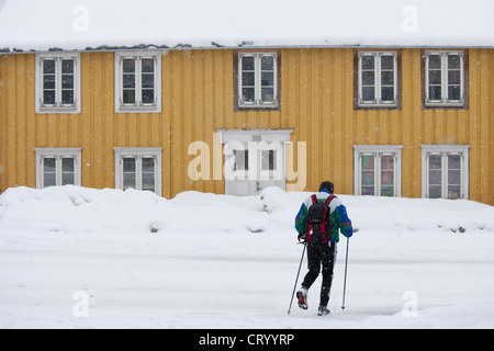 Man with walking poles passes traditional wooden buildings on Storgata in quaint area of Tromso, Arctic Circle, - Stock Photo