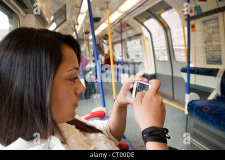 Young woman using her iPhone smartphone apps on a London Underground train, London UK - Stock Photo