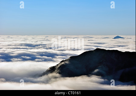 View over mountains covered in mist at sunrise seen from the Col du Tourmalet, Hautes-Pyrénées, Pyrenees, France - Stock Photo