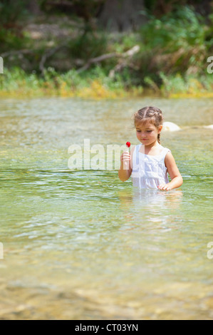 Cute little girl of five years sucking a lolipop while taking a bath in the Frio River near Concan, Texas - Stock Photo