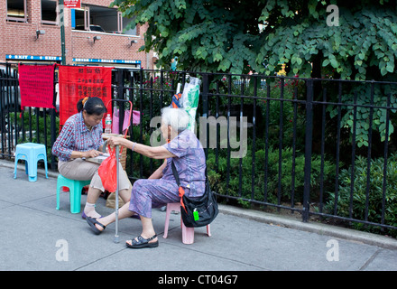 A Chinese fortune teller looks up a point of reference for an older female client on the edge of Columbus Park in - Stock Photo