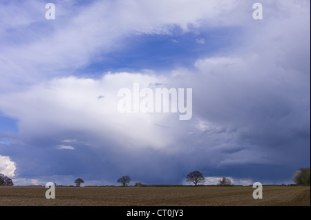 Cloud formation Cumulonimbus with Cirrus above (top left) in sky above Swinbrook in the Cotswolds, UK - Stock Photo