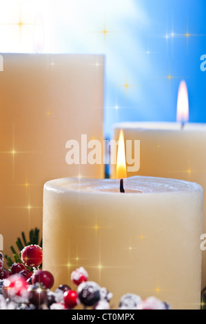 Three candles in an advent flower arrangement for advent and Christmas with golden stars - Stock Photo