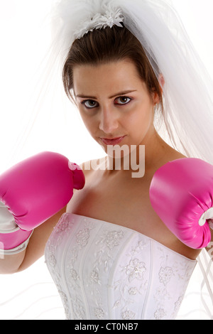 Woman in a wedding dress with boxing gloves - Stock Photo