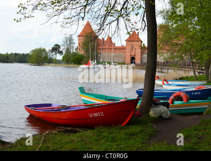 Trakai Castle most visited tourist destination in Lithuania. Wooden rowing boats, yachts and tourists near lake - Stock Photo