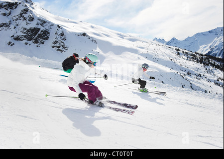 Skiers skiing together on slope - Stock Photo