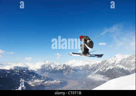 Skier jumping off snowy slope - Stock Photo