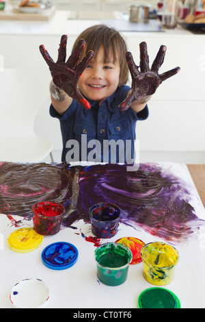 Boy finger painting on paper - Stock Photo