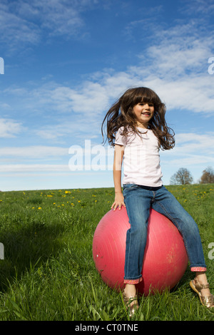 Girl playing on bouncy ball outdoors - Stock Photo