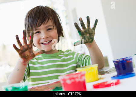 Smiling boy finger painting indoors - Stock Photo