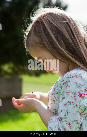 Girl examining insect on hand outdoors - Stock Photo