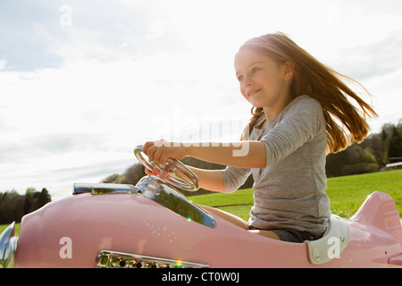 Girl driving toy airplane in field - Stock Photo