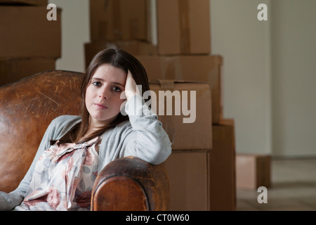 Teenage girl sitting in armchair - Stock Photo