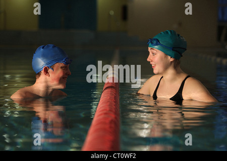 Swimmers talking in pool lanes - Stock Photo