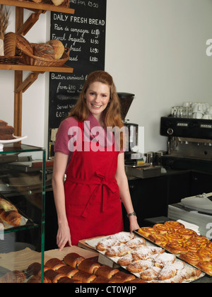Server smiling behind bakery counter - Stock Photo