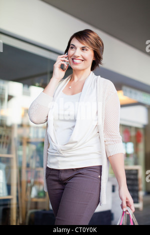 Woman talking on cell phone on street - Stock Photo
