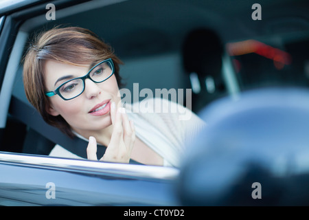 Woman checking makeup in side mirror - Stock Photo