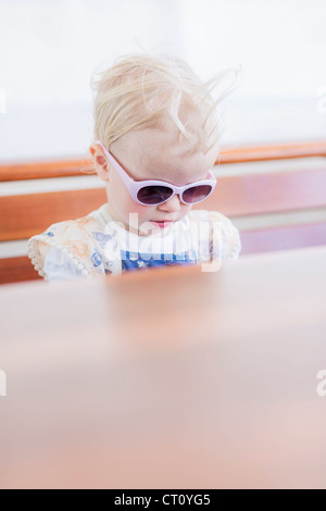 Toddler girl wearing sunglasses indoors - Stock Photo