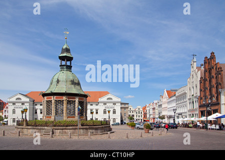 market square with Wasserkunst and restaurants Seestern and Alter Schwede, Wismar, Mecklenburg-West Pomerania, Germany - Stock Photo