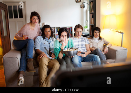 Friends watching a movie in living room - Stock Photo