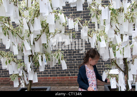 Serpentine gallery - Wish tree by Yoko Ono - child examining labels with wishes written on them