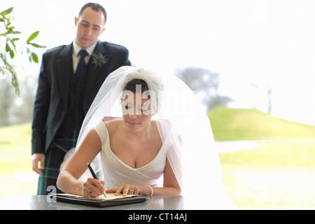 Newlywed couple signing marriage license - Stock Photo