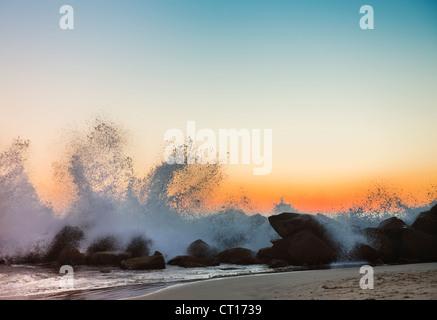 Waves crashing on rocky beach at sunset - Stock Photo