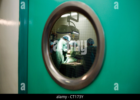 A view through an operating door window of surgical staff operating on a patient. - Stock Photo