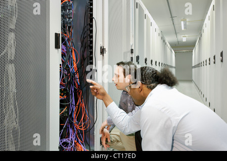 Businessmen examining wires in server Stock Photo