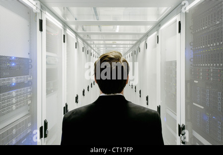 Businessman walking in server room Stock Photo