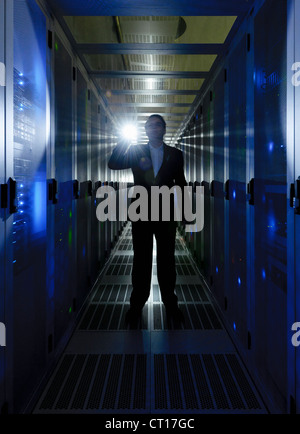 Businessman walking in server room Stock Photo