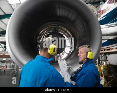 Workers talking in airplane hangar - Stock Photo
