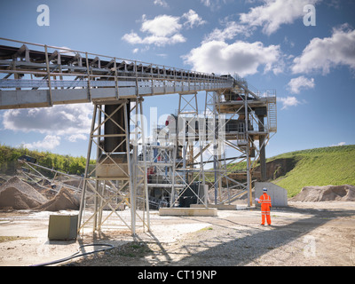 Worker standing by conveyor in quarry - Stock Photo